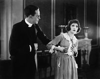 Mujer joven que lleva a cabo la mano de un hombre y que parece sorprendida (todas las personas representadas no son vivas más lar Imagen de archivo libre de regalías