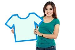 Mujer joven que lleva a cabo la muestra de la camisa Fotografía de archivo