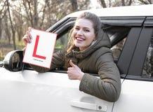 Mujer joven que lleva a cabo la muestra del conductor del principiante mientras que mira imagen de archivo libre de regalías
