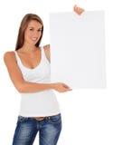 Mujer joven que lleva a cabo la muestra en blanco Imagenes de archivo