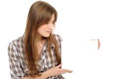 Mujer joven que lleva a cabo a la tarjeta blanca vacía, Imagen de archivo libre de regalías