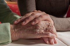 Mujer joven que lleva a cabo las manos de la mujer mayor triste con la silla de ruedas foto de archivo
