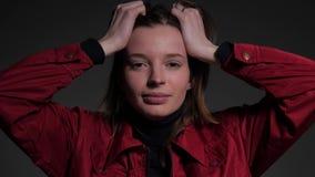 Mujer joven que lleva a cabo las manos en su cabeza metrajes