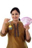 Mujer joven que lleva a cabo llave de la forma de la casa y 2000 notas de la rupia Fotografía de archivo