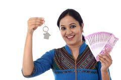 Mujer joven que lleva a cabo llave de la forma de la casa y 2000 notas de la rupia Imagenes de archivo