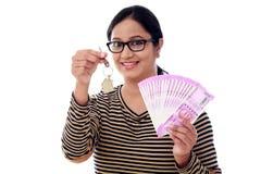 Mujer joven que lleva a cabo llave de la forma de la casa y 2000 notas de la rupia Foto de archivo