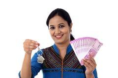 Mujer joven que lleva a cabo llave de la forma de la casa y 2000 notas de la rupia Imágenes de archivo libres de regalías