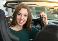Mujer joven que lleva a cabo llave del coche dentro del coche de deportes Fotografía de archivo