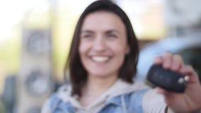 Mujer joven que lleva a cabo llaves al nuevo coche autos y que sonríe en la cámara Foco selectivo almacen de video