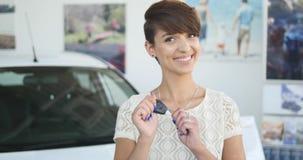 Mujer joven que lleva a cabo llaves al nuevo coche autos y que sonríe en la cámara Imagen de archivo