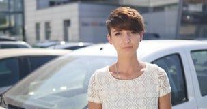 Mujer joven que lleva a cabo llaves al nuevo coche autos y que sonríe en la cámara Imágenes de archivo libres de regalías