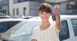 Mujer joven que lleva a cabo llaves al nuevo coche autos y que sonríe en la cámara Fotografía de archivo libre de regalías