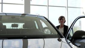 Mujer joven que lleva a cabo llaves al nuevo vehículo, sonriendo en la cámara, alegre almacen de metraje de vídeo