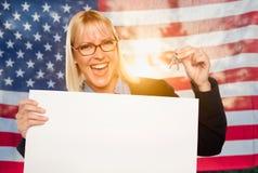 Mujer joven que lleva a cabo llaves de la casa y la muestra en blanco delante de la bandera americana imagenes de archivo