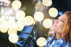 Mujer joven que lleva a cabo luces de hadas de la Navidad en la noche al aire libre adentro fotografía de archivo