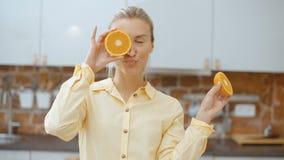 Mujer joven que lleva a cabo rebanadas anaranjadas cerca de sus ojos y sonrisa metrajes