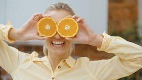 Mujer joven que lleva a cabo rebanadas anaranjadas cerca de sus ojos y sonrisa almacen de metraje de vídeo