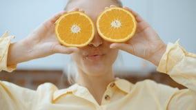 Mujer joven que lleva a cabo rebanadas anaranjadas cerca de sus ojos y sonrisa almacen de video