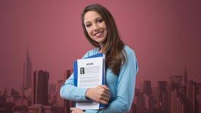 Mujer joven que lleva a cabo su curriculum vitae Fotos de archivo libres de regalías