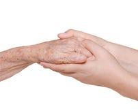 Mujer joven que lleva a cabo su mano de la abuela Fotografía de archivo