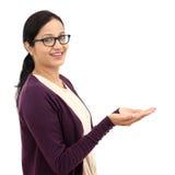 Mujer joven que lleva a cabo su mano que muestra algo Imagen de archivo