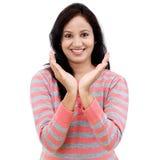 Mujer joven que lleva a cabo su mano que muestra algo Imagenes de archivo