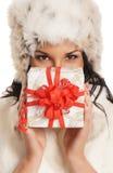 Mujer joven que lleva a cabo un regalo de Navidad Imagen de archivo libre de regalías
