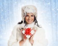 Mujer joven que lleva a cabo un regalo de Navidad Imágenes de archivo libres de regalías