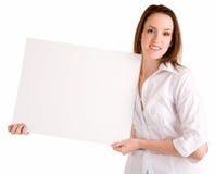 Mujer joven que lleva a cabo una muestra blanca en blanco Imagen de archivo libre de regalías