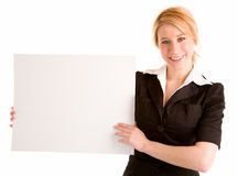 Mujer joven que lleva a cabo una muestra blanca en blanco Imagen de archivo