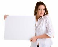 Mujer joven que lleva a cabo una muestra blanca en blanco Imágenes de archivo libres de regalías