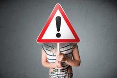 Mujer joven que lleva a cabo una señal de tráfico de la exclamación foto de archivo