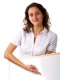 Mujer joven que lleva a cabo a una tarjeta blanca Fotos de archivo