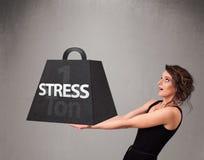 Mujer joven que lleva a cabo una tonelada de peso de la tensión Imágenes de archivo libres de regalías