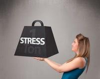 Mujer joven que lleva a cabo una tonelada de peso de la tensión Imagen de archivo libre de regalías