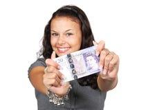 Mujer joven que lleva a cabo veinte libras foto de archivo libre de regalías