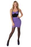 Mujer joven que lleva el cortocircuito apretado Mini Dress de la púrpura y los zapatos del tacón alto Fotos de archivo libres de regalías