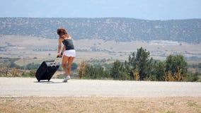 Mujer joven que lleva el equipaje pesado almacen de video