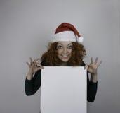 Mujer joven que lleva el sombrero de Papá Noel que lleva a cabo la muestra vacía Imágenes de archivo libres de regalías