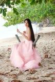 Mujer joven que lleva el vestido rosado largo en la playa hawaiana Imagenes de archivo