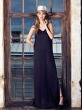 Mujer joven que lleva el vestido y el sombrero negros largos Foto de archivo