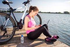 Mujer joven que lleva en la camisa rosada que se sienta en el puente del lago usando el ordenador portátil Fotos de archivo libres de regalías