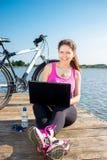 Mujer joven que lleva en la camisa rosada que se sienta en el puente del lago usando el ordenador portátil Imagenes de archivo