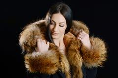 Mujer joven que lleva la chaqueta lujosa de la piel imagen de archivo