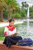 Mujer joven que lleva la falda y la blusa andinas tradicionales con el collar rojo a juego, asistiendo en banco al lado del lago Fotos de archivo libres de regalías