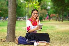 Mujer joven que lleva la falda y la blusa andinas tradicionales con el collar rojo a juego, asistiendo en hierba al lado de árbol Imagenes de archivo