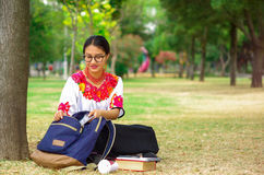 Mujer joven que lleva la falda y la blusa andinas tradicionales con el collar rojo a juego, asistiendo en hierba al lado de árbol Foto de archivo