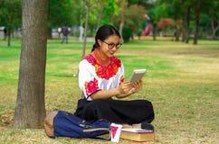 Mujer joven que lleva la falda y la blusa andinas tradicionales con el collar rojo a juego, asistiendo en hierba al lado de árbol Imagen de archivo libre de regalías