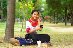 Mujer joven que lleva la falda y la blusa andinas tradicionales con el collar rojo a juego, asistiendo en hierba al lado de árbol Imágenes de archivo libres de regalías