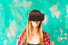 Mujer joven que lleva las auriculares de la realidad virtual foto de archivo
